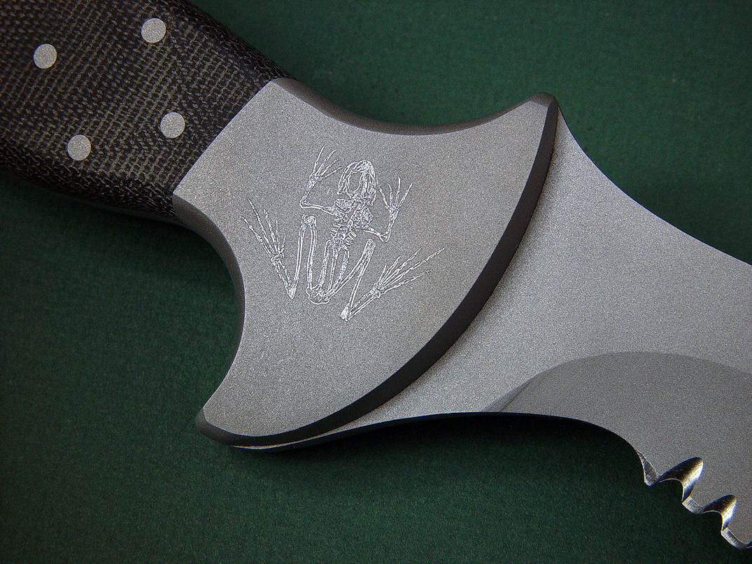 "Bone Frog engraving on ""Horus"" bolster, reverse  side view in ATS-34 high molydenum stainless steel blade, 304 stainless steel bolsters, engraved, Micarta phenolic handle, locking kydex, aluminum, stainless steel sheath with black lacquered brass engraved flashplate."