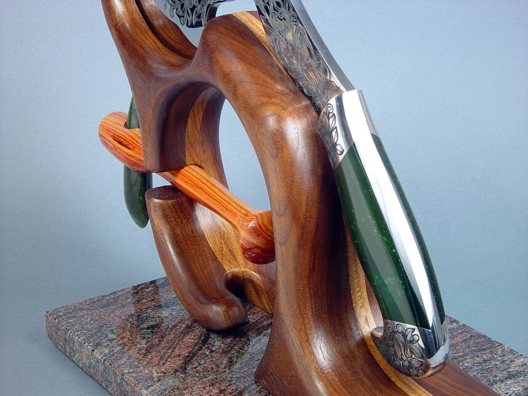 Manaya, petaloid celt position in display stand of walnut, oak, and granite