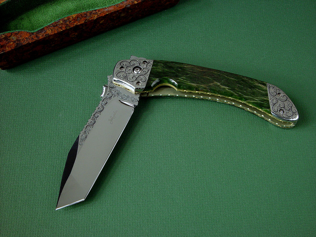 """Procyon"" liner lock folding knife, obverse side view,in hand-engraved ATS-34 high molybdenum stainless steel blade, hand-engraved 304 stainless steel bolsters, anodized 6AL4V titanium liners and lockplate, Pounamu New Zealand Greenstone Nephrite Jade gemstone handle, case of Granite, Quartz Terrazzo composite"