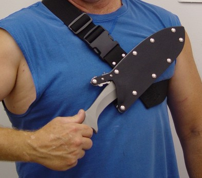 Unlocking and removing the tactical combat knfe from the locking sheath in the sternum harness