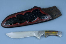 """Golden Eagle"" custom knife, stand view in CPM154CM high molybdenum stainless steel blade, hand-engraved 304 stainless steel bolsters, Australian Tiger Iron gemstone handle, hand-carved, hand-dyed leather sheath inlaid with Caiman skin, stand of Ponderosa Pine burl and Red Oak"